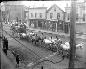 Horses, wagon and band on parade near the Flatiron Block.