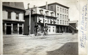 Frank Moore on Main Street near the Border City Hotel. Bike not really a velocipede, known as a high wheel bicycle